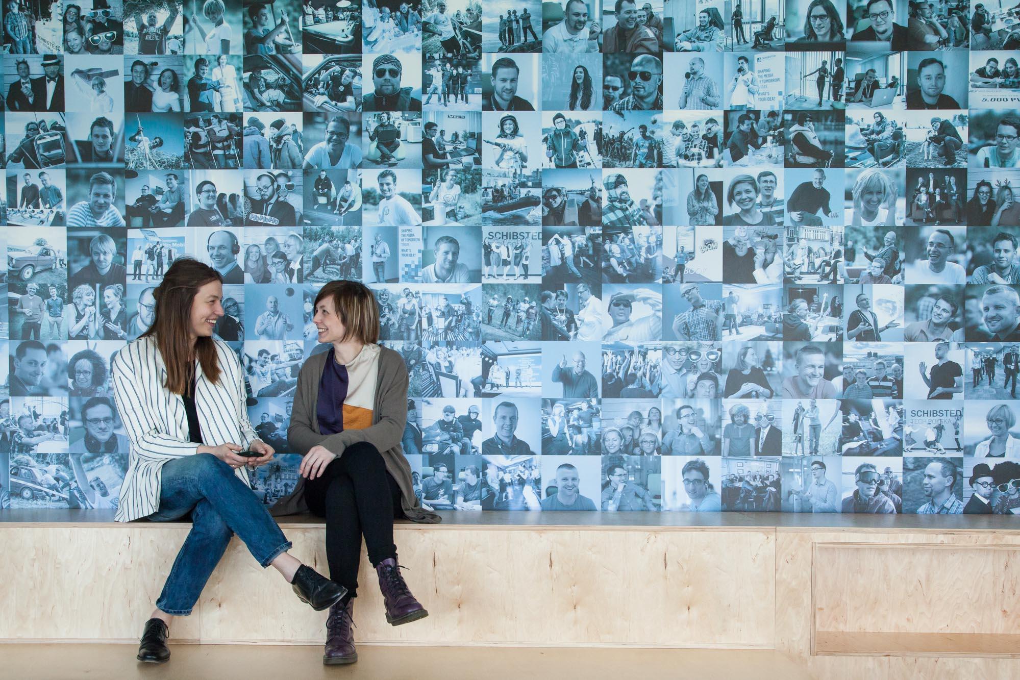 Natalia Szczesniak and Anna Danielewska-Tułecka chatting in front of the wall with 216 photos of employees. Photo: John Einar Sandvand